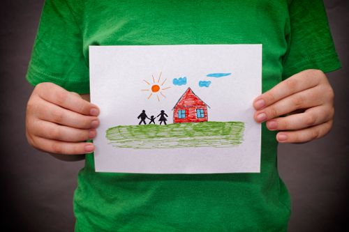 Adoption Law in North Carolina - Child holds a drawn house with family.