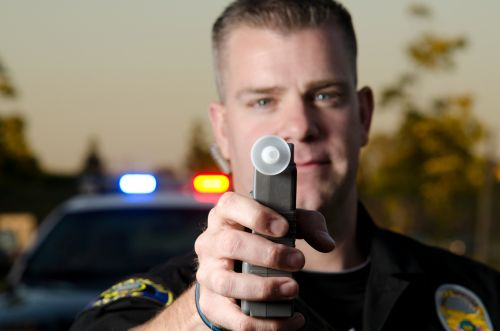 A police officer holds the breath test machine for a suspect to blow into with a police car in the background.