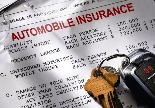 Auto Insurance policy with keys and glasses